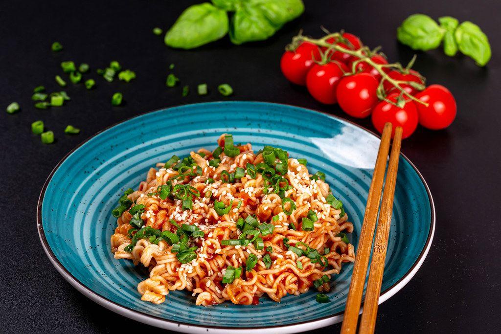 Spaghetti with tomato sauce, sesame seeds and chopsticks