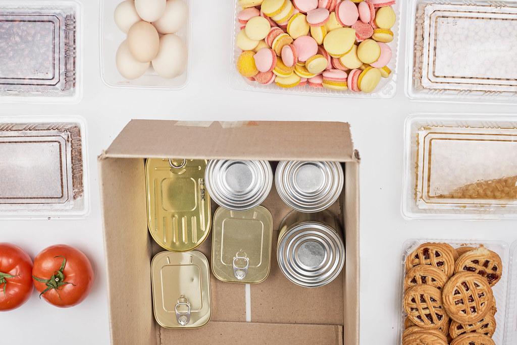 Spende für die Tafel: Blechdosen in einem Karton mit Tomaten, Eiern, Keksen und Trockenfrüchten