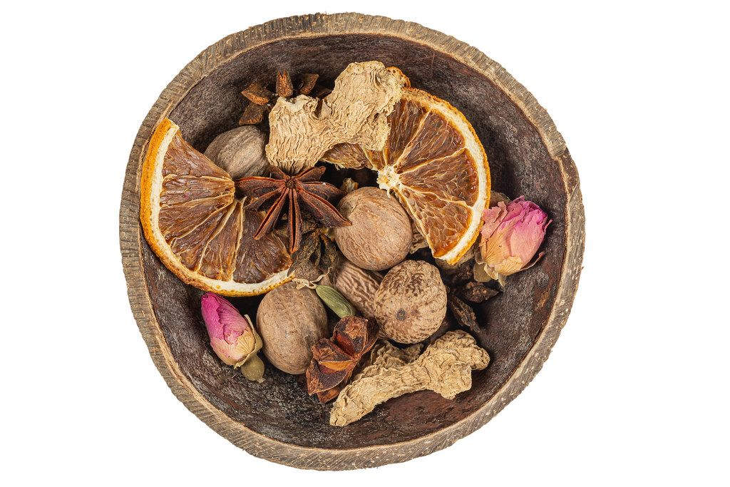 Spices for mulled wine in a wooden bowl, top view