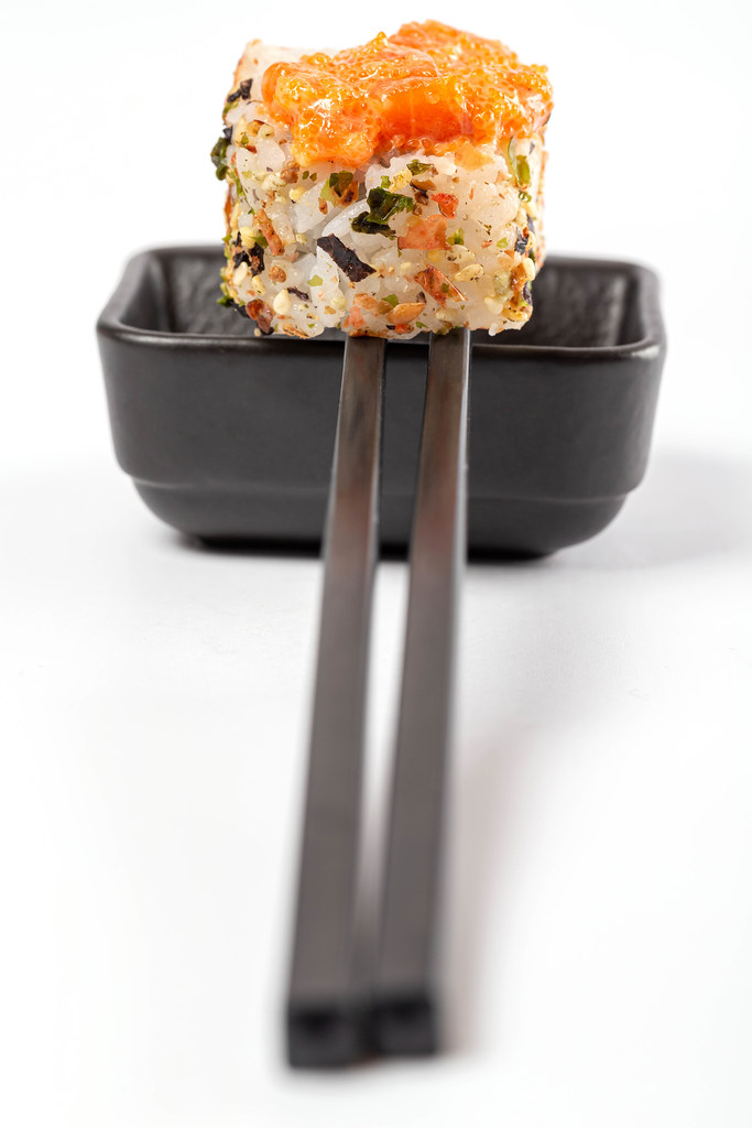 Spicy roll with tobiko caviar, sauce and chopsticks