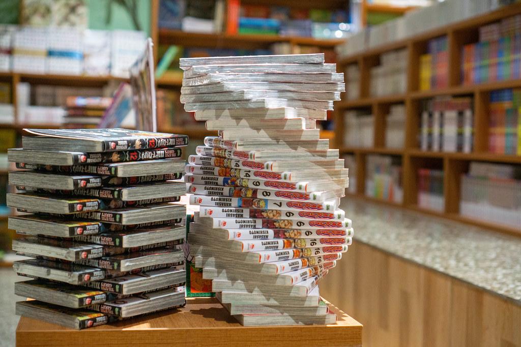 Spirale aus Manga Büchern der Buchserie Naruto neben einem Stapel aus Comic Büchern auf einem Tisch in einem Buchladen
