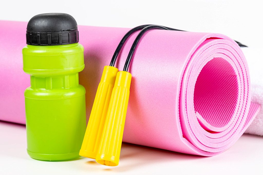 Sport lifestyle concept - yoga mat, jump rope and water bottle on white background