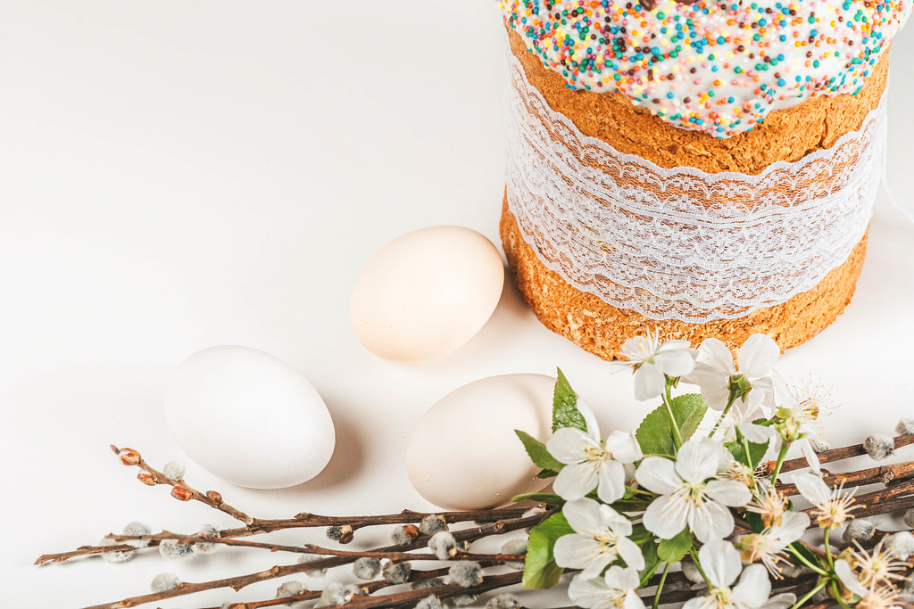 Spring branches of cherries and willows with easter cake and eggs