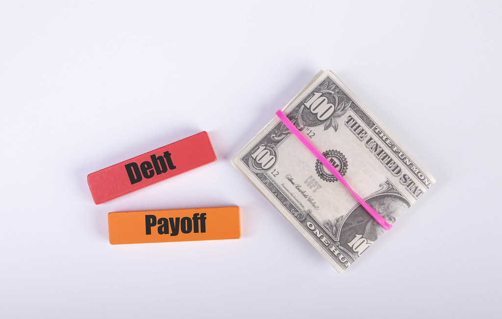 Stack of cash with Debt and Payoff text