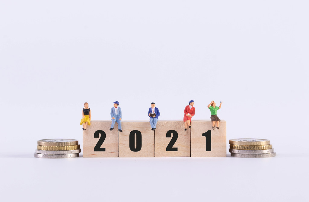 Stack of coins and group of people sitting on wooden cubes with 2021 text on white background