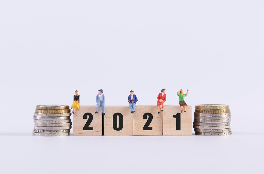 Stack of coins and group of people sitting on wooden cubes with 2021 text