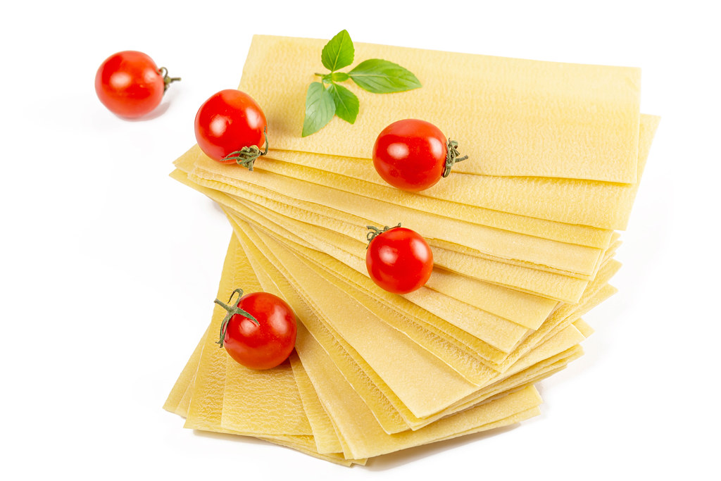 Stack of dried lasagna sheets with cherry tomatoes and basil