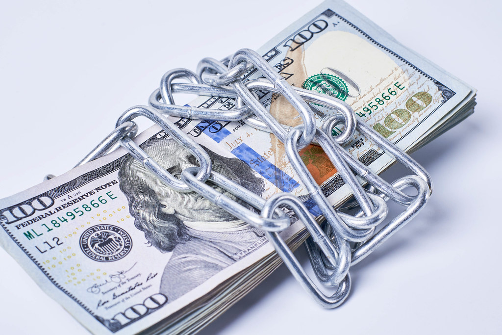 Stack of money wrapped by metal chain on white background