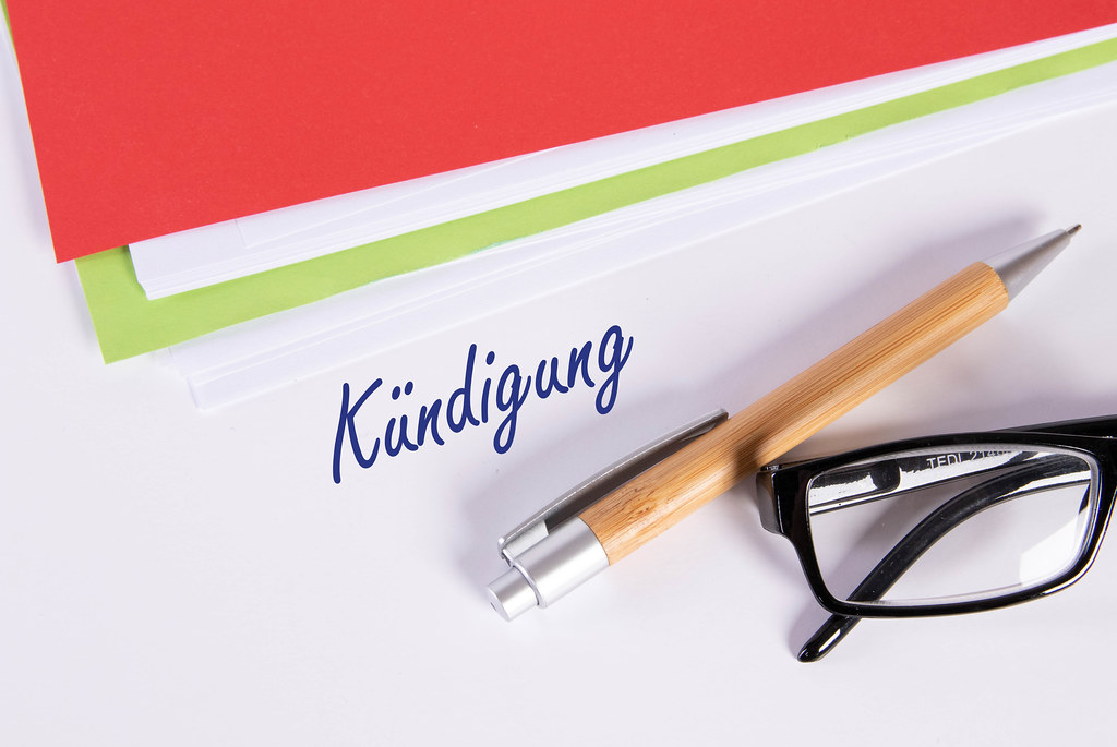 Stack of papers with glasses, pen and Kündigung text