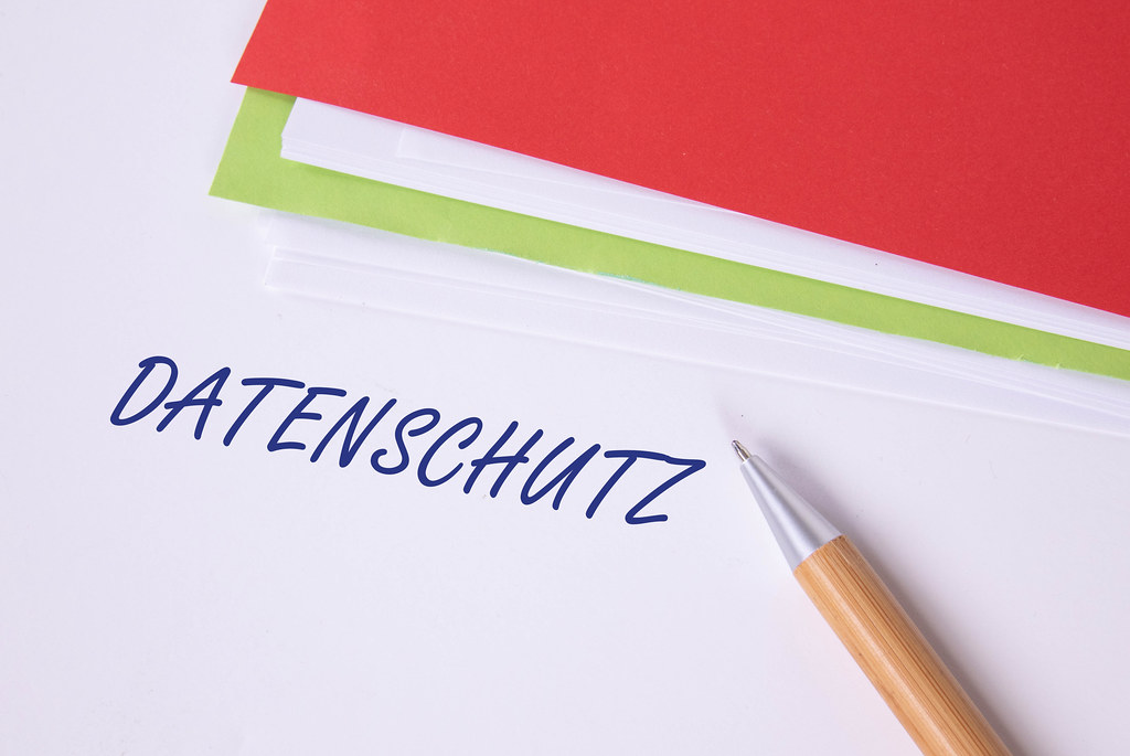 Stack of papers with pen and Datenschutz text