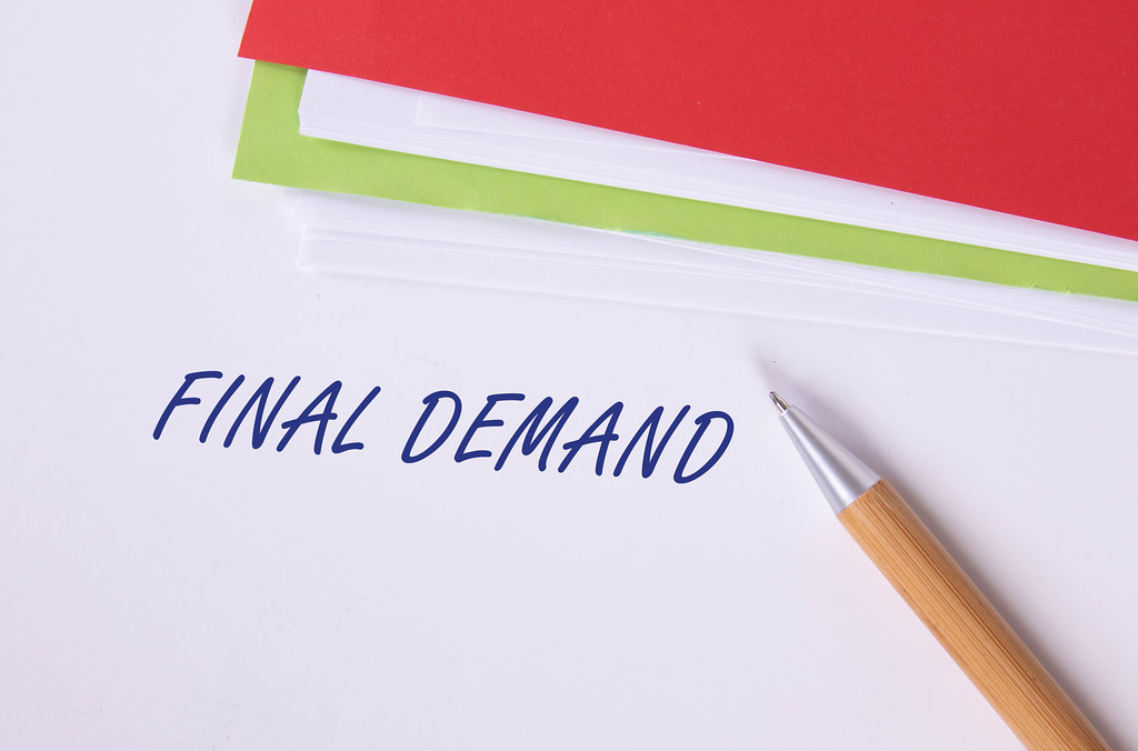 Stack of papers with pen and Final Demand text