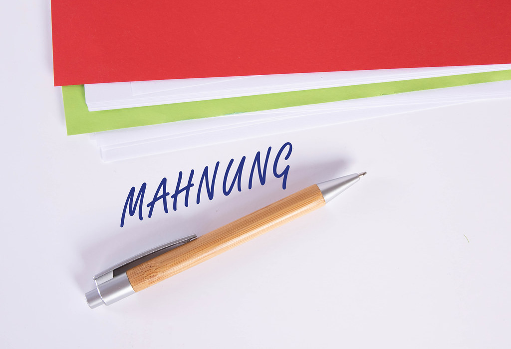 Stack of papers with pen and Mahnung text