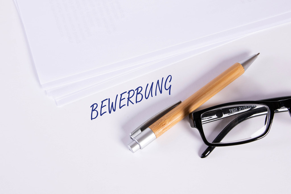 Stack of papers with pen, glasses and Bewerbung text