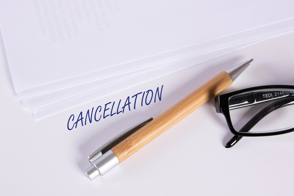 Stack of papers with pen, glasses and Cancellation text