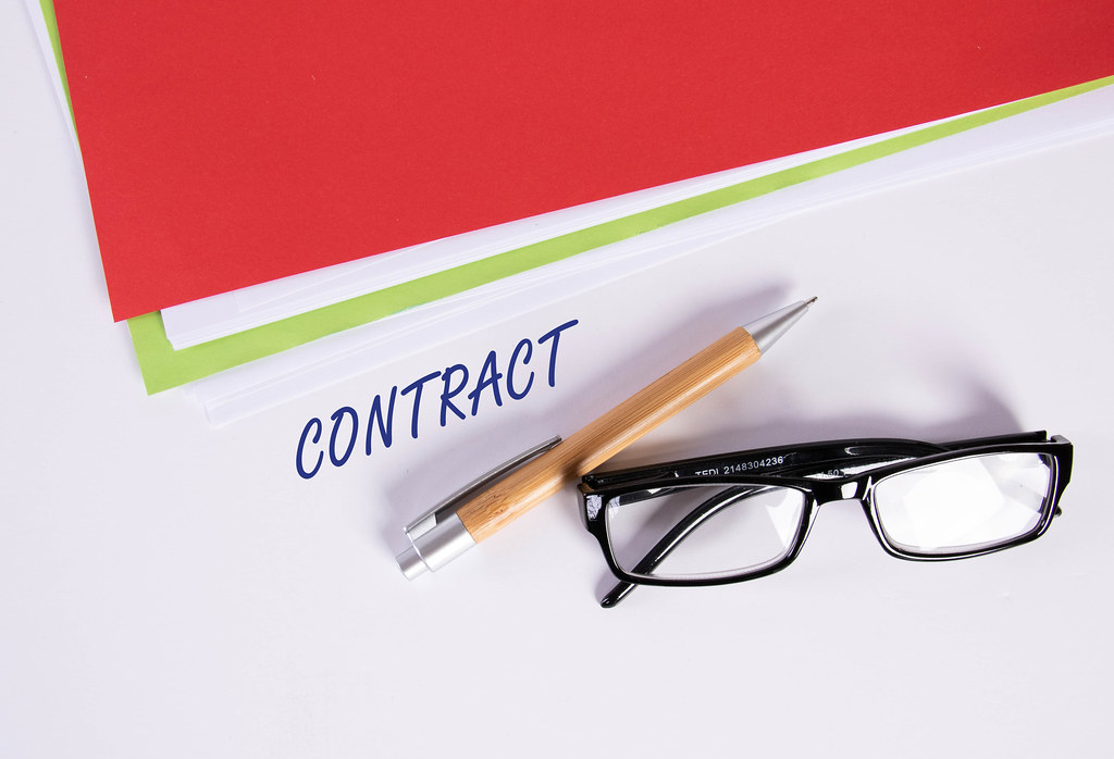 Stack of papers with pen, glasses and Contract text
