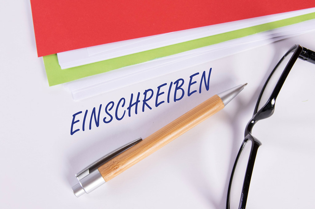 Stack of papers with pen, glasses and Einschreiben text