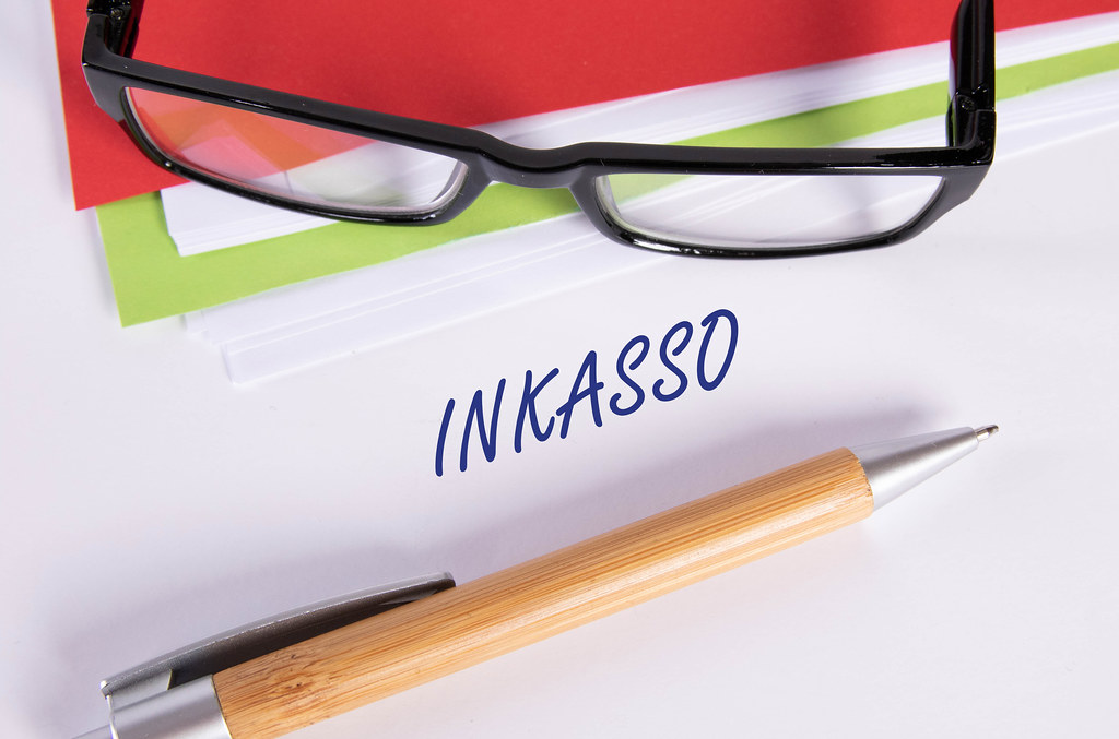 Stack of papers with pen, glasses and Inkaso text