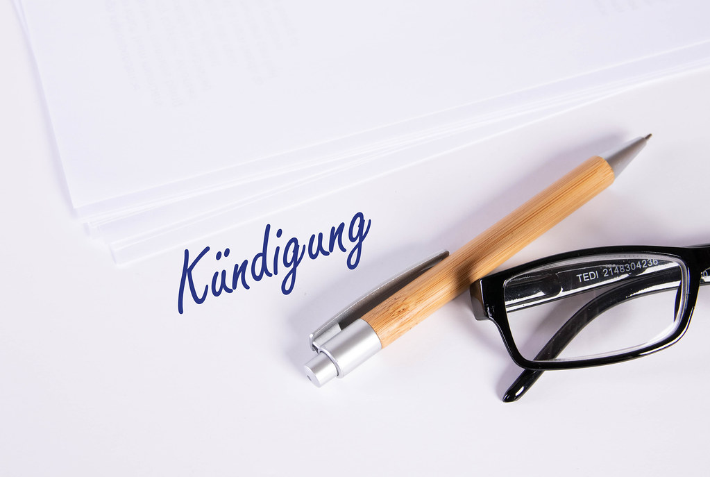 Stack of papers with pen, glasses and Kündigung text