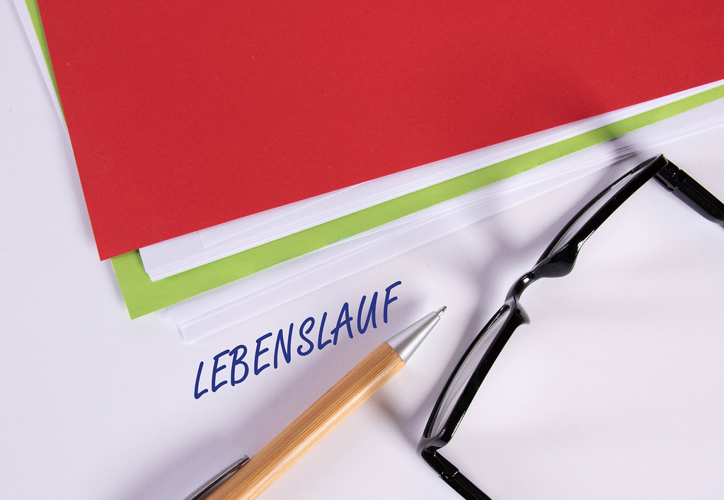 Stack of papers with pen, glasses and Lebenslauf text