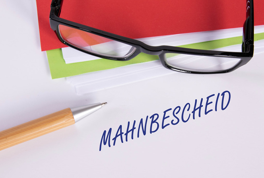 Stack of papers with pen, glasses and Mahnbescheid text