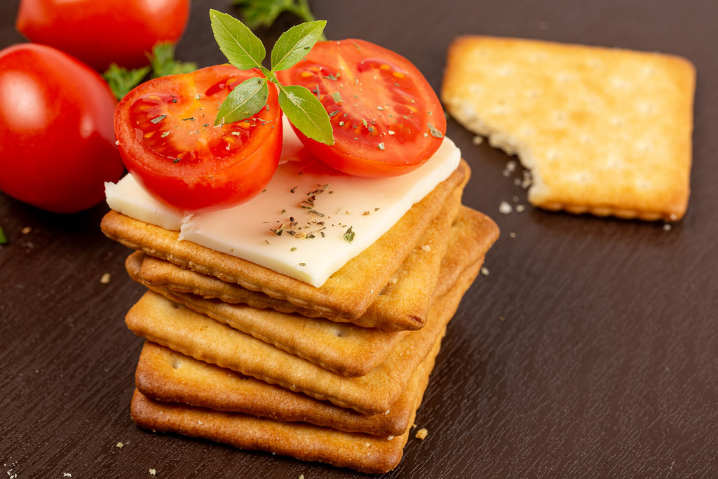 Stack of square crackers with slices of cheese, tomato and basil