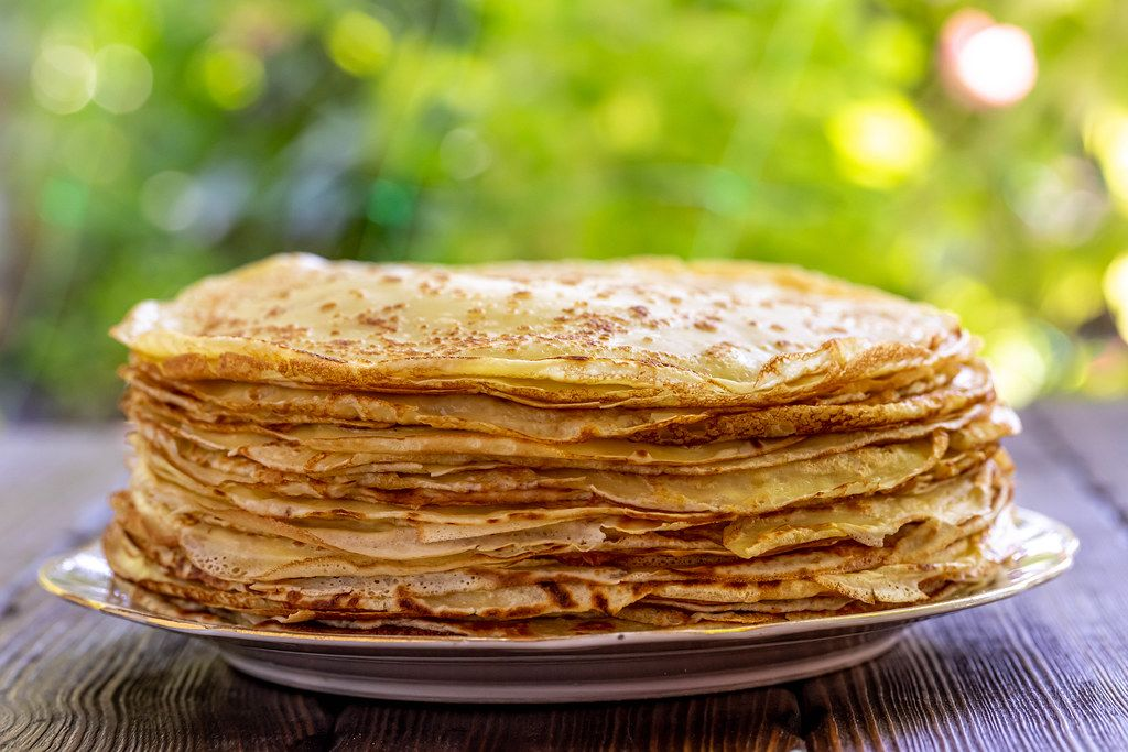 Stack pancakes on brown wooden table with green nature bokeh background