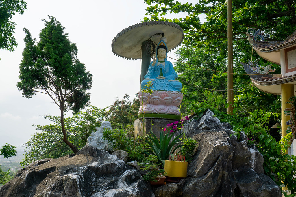 Statue of Sitting Lady Buddha and Laughing Buddha on a Small Rock in front of Tam Ton Pagoda at Marble Mountains in Da Nang, Vietnam