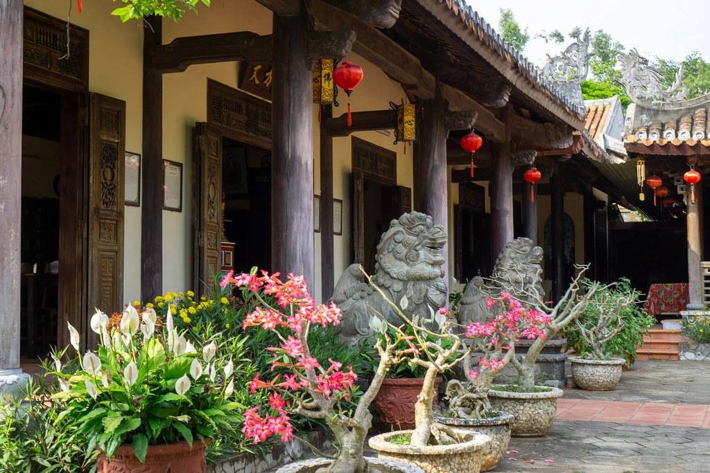 Statuen von Chinesischen Wächterlöwen und Blumentöpfe mit Bäumen und Pflanzen vor der Tam Ton Pagode bei den Marble Mountains in Da Nang, Vietnam