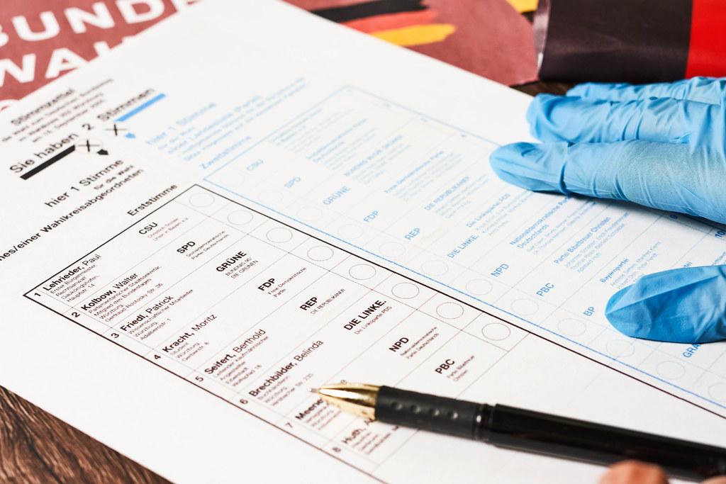 Stift und Hand mit Einmalhandschuhe auf dem Stimmzettel für die Bundestagswahl in Corona-Zeit