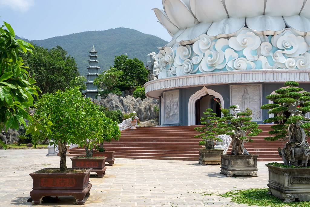 Stone Flower Pots with Small Bonsai Trees in front of the Lady Buddha Statue at Linh Ung Pagoda with Mountains in the Background in Da Nang, Vietnam