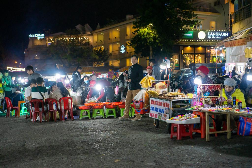Straßenküchen und Verkaufsstände mit einigen Menschen auf dem Dalat Nachtmarkt in Da Lat, Vietnam
