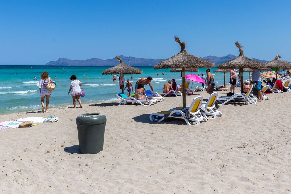 Straw parasols and plastic sun beds. Tourists on the sandy beach of Can Picafort on the island of Mallorca