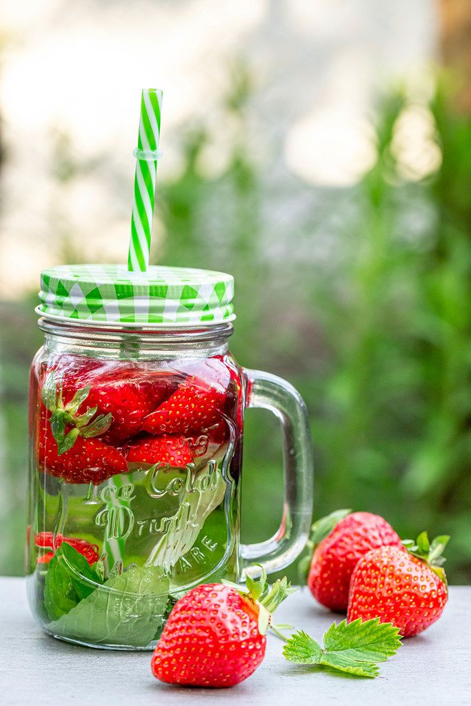 Strawberry drink in a glass jar on a blurred background of nature
