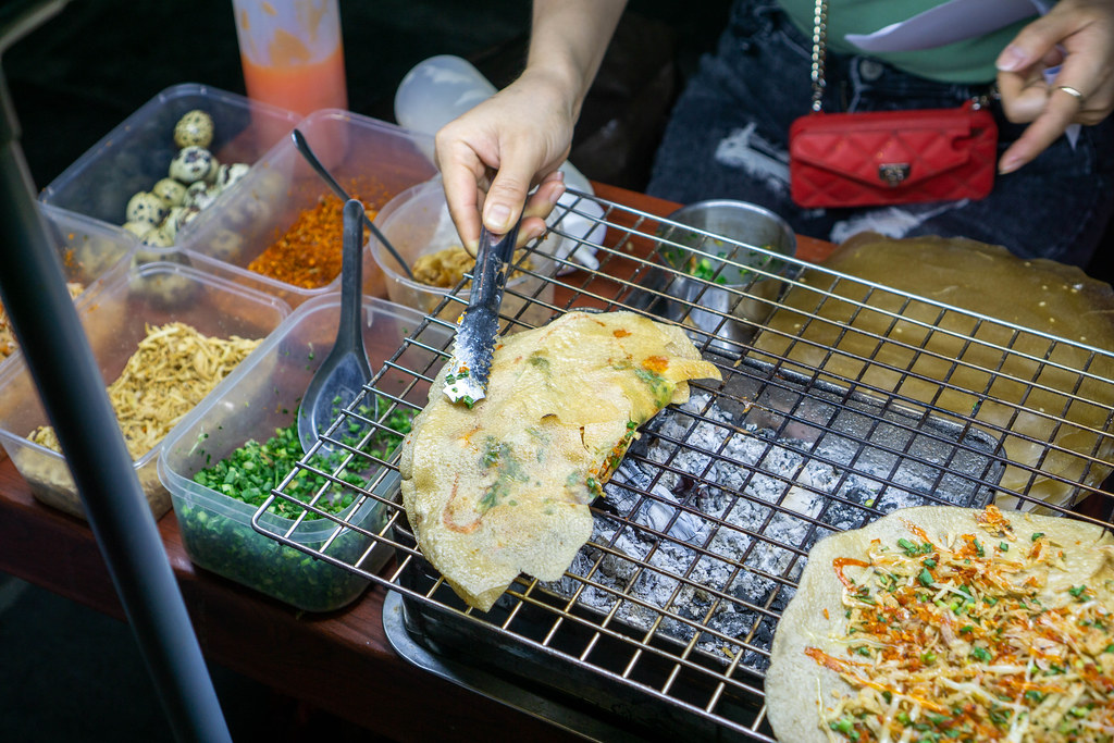 Street Food Seller preparing Vietnamese Pizza Banh Trang Nuong on a Barbecue Grill with Quail Eggs, Chili, Shrimps, Spring Onions, Fried Onions and Mayonnaise in Hoi An, Vietnam