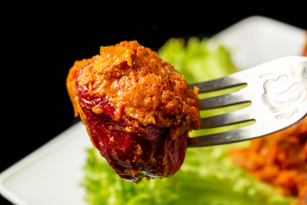 Stuffed bell peppers with meat, rice and tomato sauce on a fork, close-up