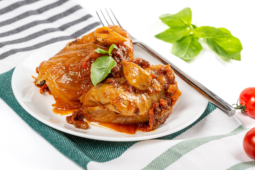 Stuffed cabbage rolls with tomato sauce on white plate