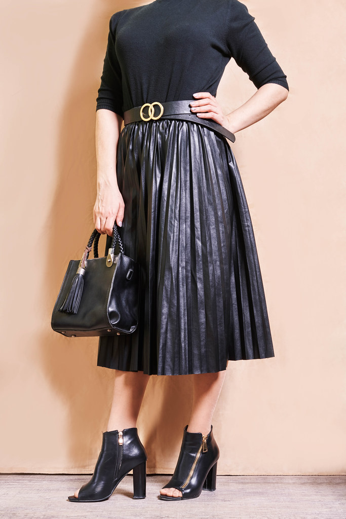 Stylish beautiful woman in a luxurious beautiful black pleated skirt