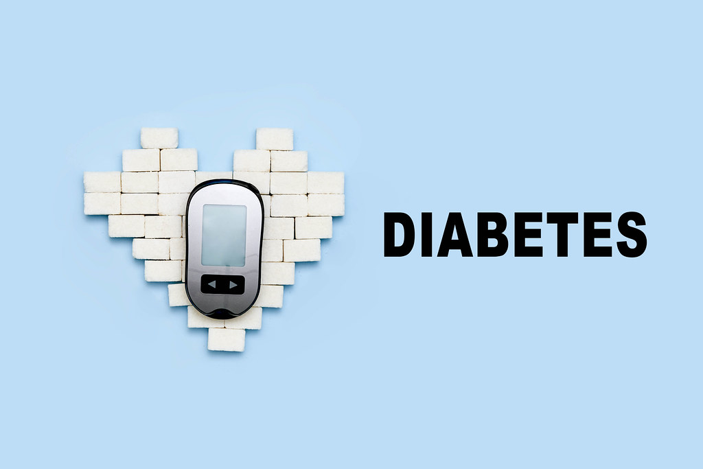 Sugar cubes and portable diabetes measuring monitor on bright blue backdrop