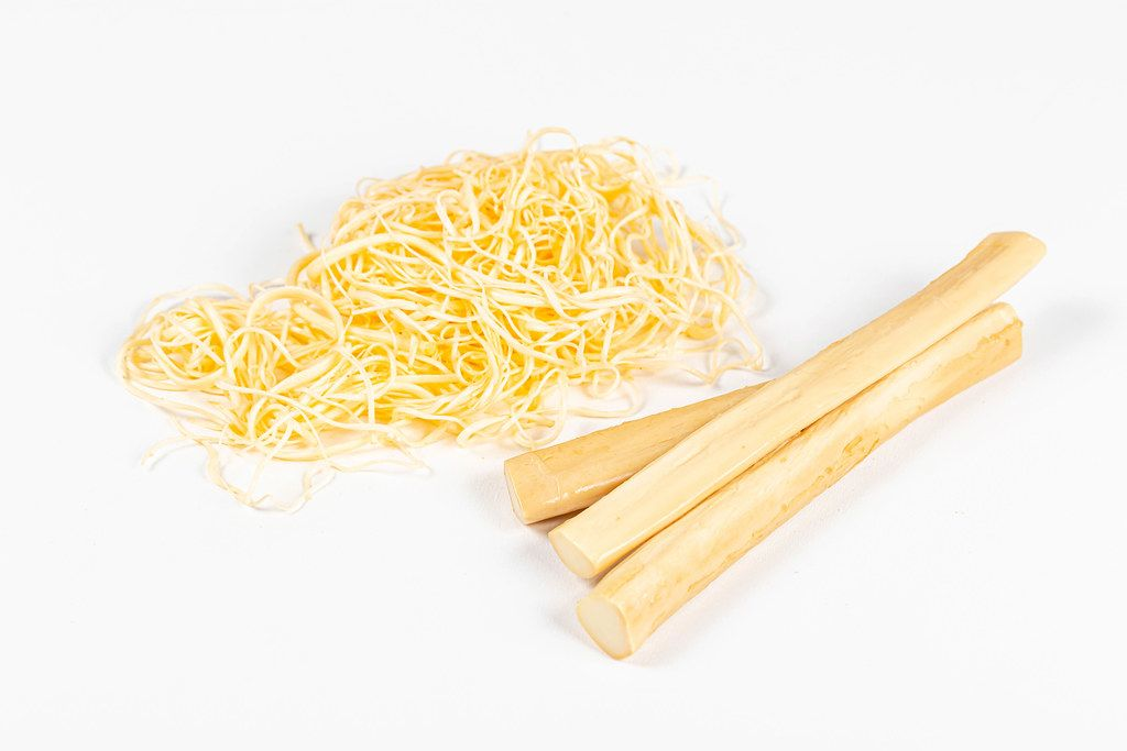 Suluguni cheese sticks and shavings on a white background