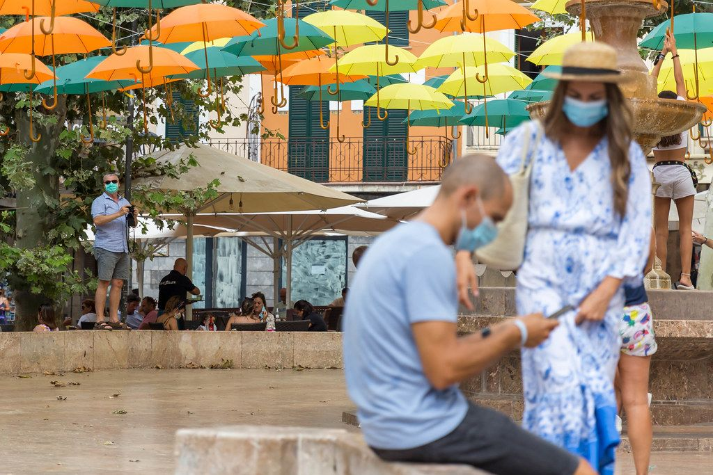 Summer 2020: tourists with face mask, smartphone or camera under the suspended umbrellas in Sóller