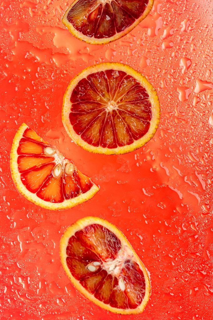 Summer red fruit background with ripe sicilian orange slices