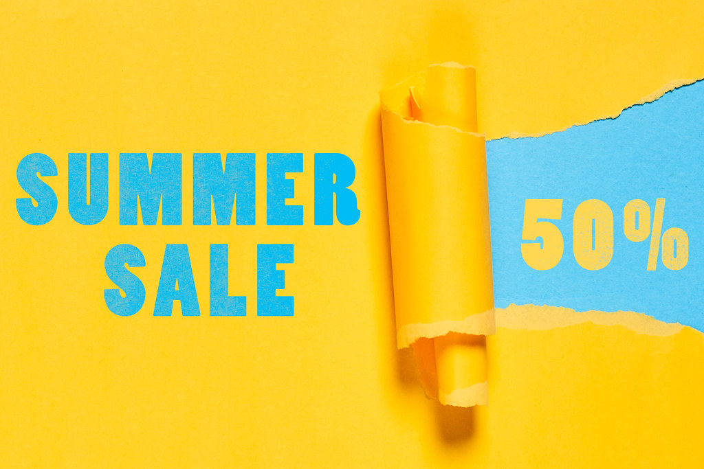 Summer sales with 50 percent discount on paper hole with torn edges
