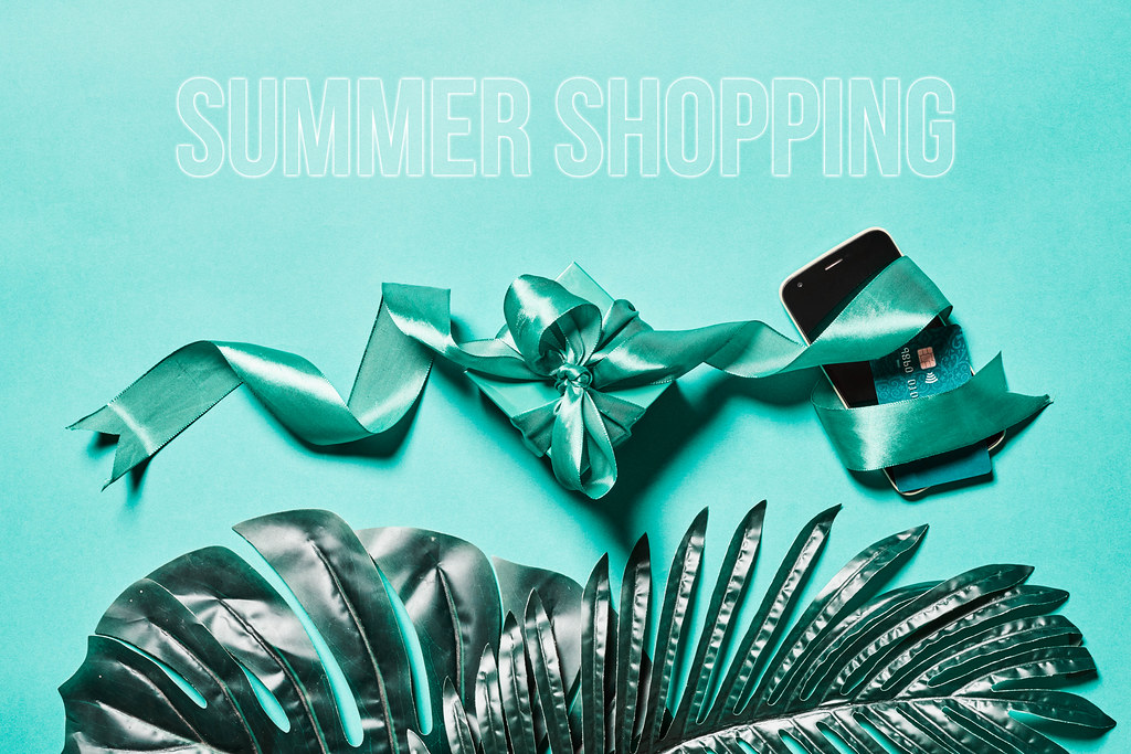 Summer shopping - palm leaves, credit card with smartphone and gift from the online store