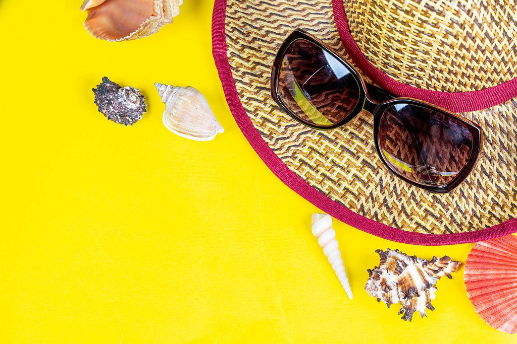 Summer vacation concept. Hat, sunglasses and shells on a yellow background with free space
