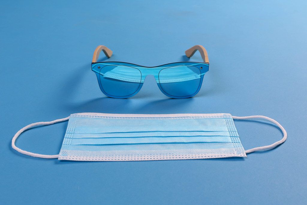 Sunglasses and medical face mask on blue background