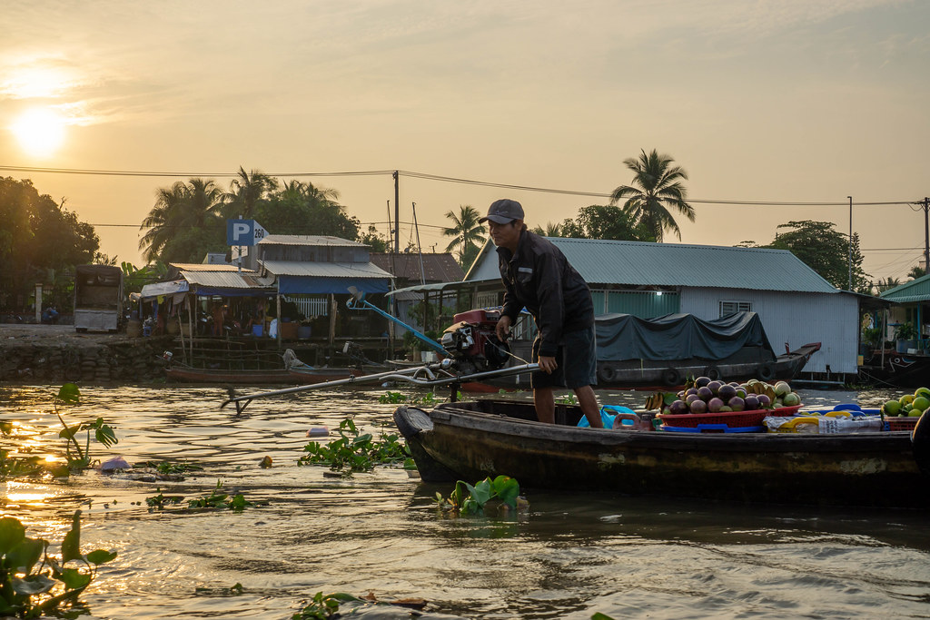 Sunrise at Cai Rang Floating Market with Vietnamese Man on a Wooden Boat selling Fresh Fruits in Can Tho, Vietnam