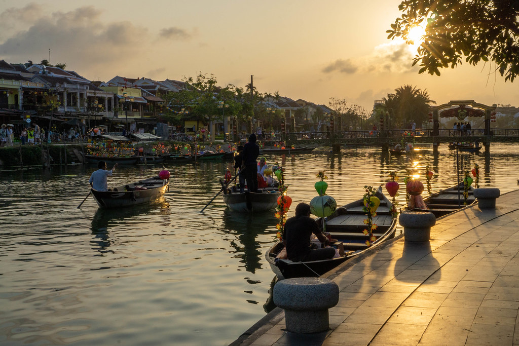 Sunset in the Ancient Town of Hoi An, Vietnam with Decorated Wooden Tourist Boats going towards the Bridge of Light at Golden Hour