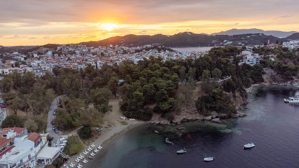 Sunset light over Greek island Skiathos: bird's eye view of the town and the coast with boats and trees