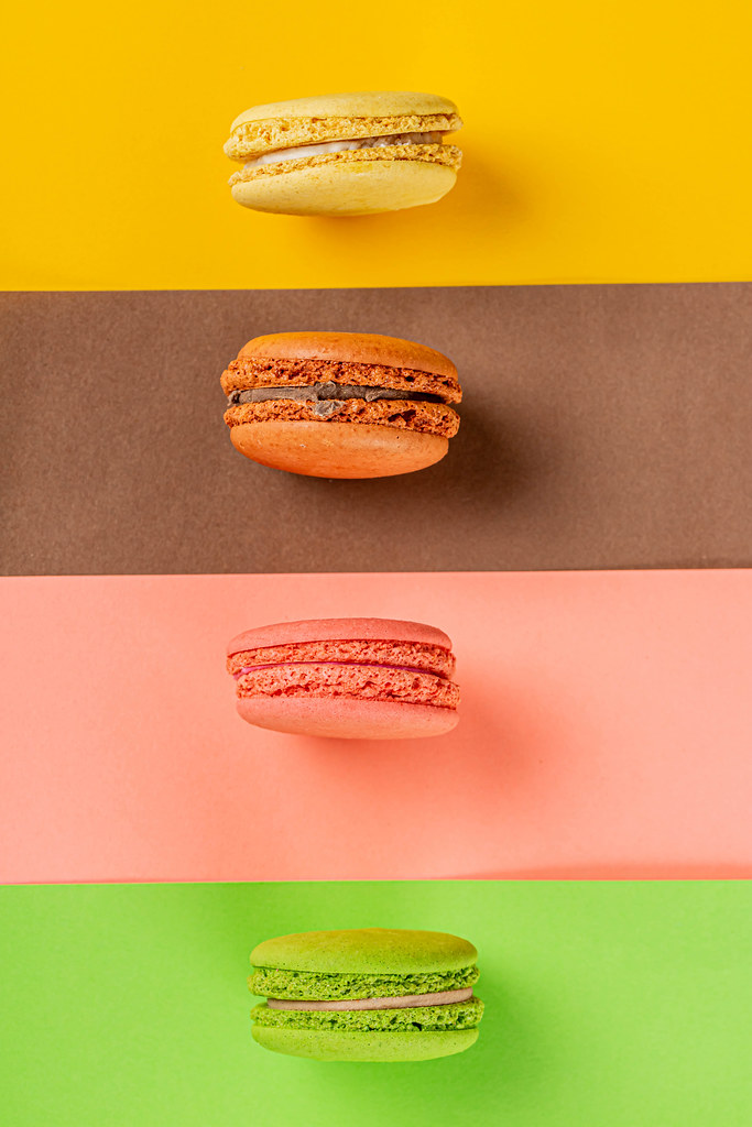 Sweet and colourful french macaroons on a colored background, top view
