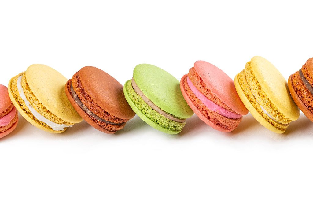 Sweet dessert background with fresh macaroons on white